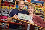 Couple Holding Framed Dollar Bill in Skateboard Store