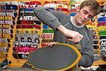 Man Adjusting Wheel on Skateboard