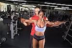 Frau Aufhebung Gewichte mit Personal Trainer