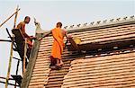 Buddhist Monks Repairing Roof Of Wat Choum Khong, Luang Prabang, Laos
