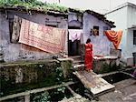 Femme suspendue à l'extérieur, blanchisserie, Varanasi, Inde