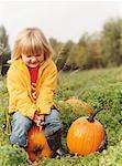 Child Sitting on Pumpkin in Field