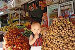 Enfant debout à l'extérieur du magasin, Can Tho, Vietnam