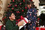 Brother Handing Sister Present on Christmas Morning