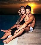 Couple embrasser au bord d'une piscine au coucher du soleil
