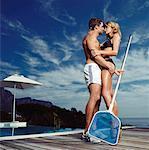 Pool Boy Embracing Woman in Bikini