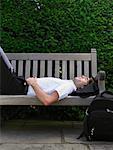 Homme couché sur le banc de parc