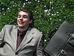 Homme d'affaires allongé sur l'herbe