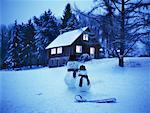 Deux bonhommes de neige à l'extérieur de la cabane en rondins