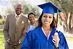 Portrait einer Frau in einem Kleid Graduation, ihrer stolzen Eltern im Hintergrund stehend