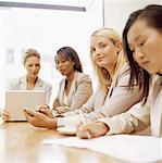 vier Geschäftsfrauen sitzen in einem Konferenzraum