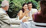 newlywed couple raising a toast at a wedding reception