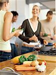 zwei junge Frauen und zwei junge Männer stehen gemeinsam in der Küche