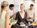 zwei junge Frauen kochen mit zwei junge Männer hinter ihnen steht in der Küche