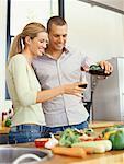 junger Mann Gießen Rotwein in ein Glas, gehalten von einer jungen Frau in der Küche