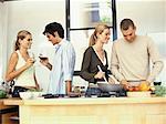 junges Paar mit einem anderen jungen Paar Kochen und trinken Rotwein in der Küche