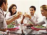 vier Jugendliche feiern mit Weißwein