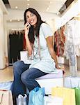 Seitenansicht einer jungen Frau, das Gespräch auf ein Mobiltelefon in ein Bekleidungsgeschäft
