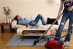 Woman Vacuuming while Man Sleeps on Sofa