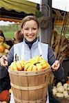 Femme transportant panier de citrouilles