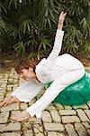Frau tun erstreckt sich auf gymnastikball im freien