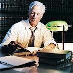 Mature avocat assis à une Table et travailler tard dans une bibliothèque