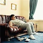 Jeune homme se trouve rabattu sur un canapé à regarder des vidéos et en maintenant un paquet de chips