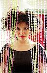 Femme funky furtivement à travers Rideau perlé