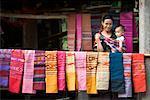 Porträt Frau Verkauf von Textilien, tragen Baby, Laos