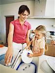 Gros plan d'une mère et sa fille, laver la vaisselle