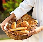 breadmaker with basket of fresh baguettes