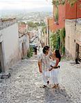 Couple Walking Up Cobblestone Street, Mexico