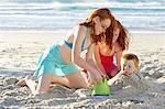 Girls Burying Boy in Sand