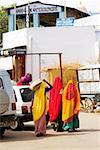 Rear view of three women walking on the streets, Pushkar, Rajasthan, India