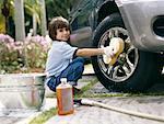 Boy (5-7) washing car on driveway smiling, portrait