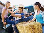 Deux jeunes femmes à l'écoute d'un jeune homme jouant de la guitare