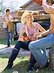 Jeune femme regardant un jeune homme boire dans une fiole