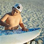 Boy Waxing Surfboard