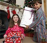 Mädchen und jungen (5-7) sitzen am Herd, präsentiert Weihnachten halten