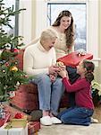 Grand-mère et petites-filles d'échanger des cadeaux de Noël