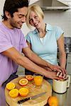 Couple in kitchen, making orange juice, woman smiling, portrait