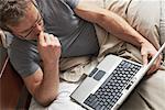 Homme utilisant un ordinateur portable dans le lit