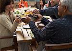 Femme en passant le bol au dîner de famille à l'extérieur