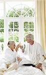 Couple d'âge mûr boire le Champagne au lit