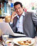 Homme d'affaires au Restaurant avec ordinateur portable et téléphone cellulaire