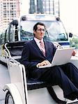 Homme d'affaires avec ordinateur portable, assis en Rickshaw
