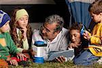 Senior man and his four grandchildren near a tent