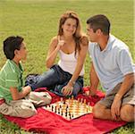 Profil de côté d'un petit garçon assis avec ses parents et jouer aux échecs