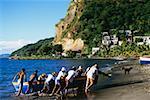 Indigènes poussant un bateau sur un rivage près de la ville de Castries, Sainte-Lucie