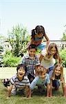 Groupe d'enfants formant une pyramide humaine à l'extérieur